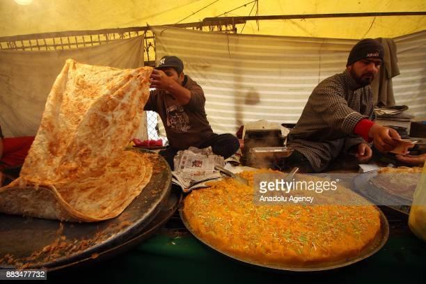 Road side venders prepare snacks outside the shrine as Kashmiri Muslim worshippers take part in the celebrations for Mawlid alNabi the birth...