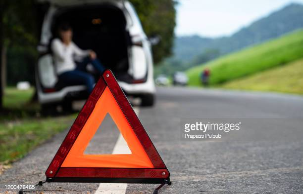 road side warning triangle, warning oncoming traffic of a broken down car, - traffic accident stock pictures, royalty-free photos & images
