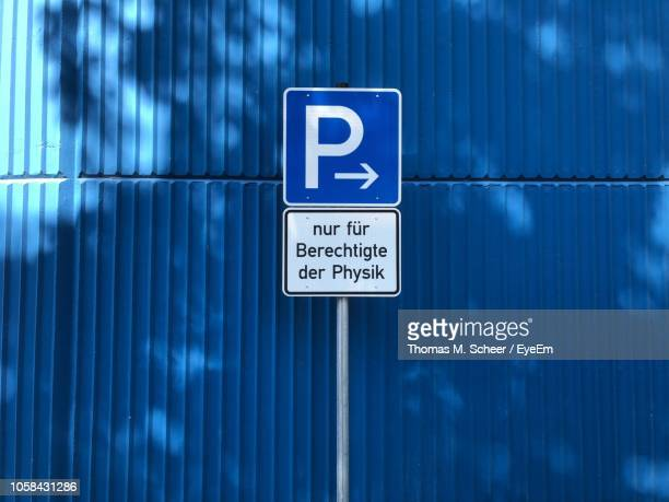 road sign against blue wall - niet westers schrift stockfoto's en -beelden