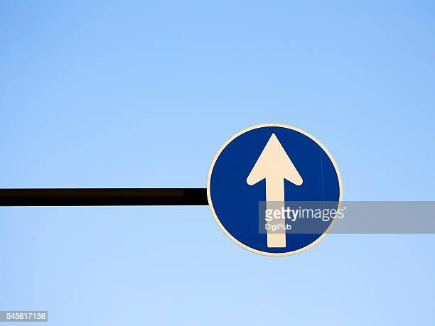 road sign against clear sky - curved arrows stock-fotos und bilder