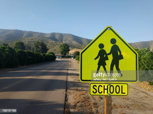 road sign against sky - pedestrian crossing sign stock photos and pictures