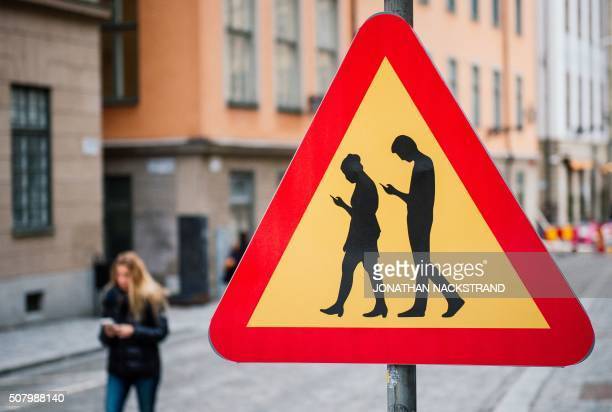 TOPSHOT A road sign Warning Against pedestrians focusing on their smartphones is pictured on February 2 2016 near the old town in Stockholm / AFP /...