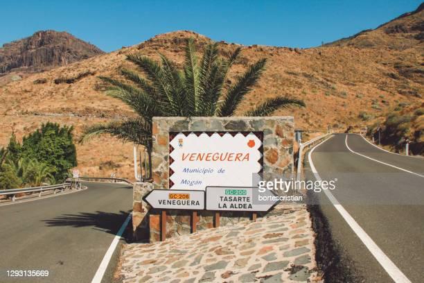 road sign by mountains against clear sky - bortes fotografías e imágenes de stock