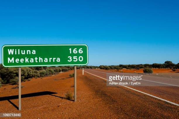 road sign by road against clear blue sky - road sign stock pictures, royalty-free photos & images