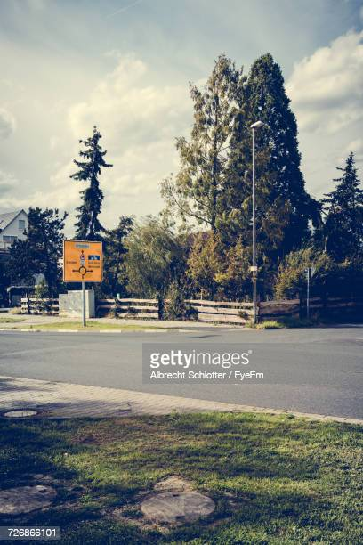 road sign by street against sky - albrecht schlotter stock photos and pictures