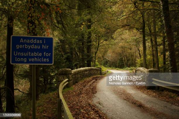 road sign by trees in forest - lake vyrnwy stock pictures, royalty-free photos & images