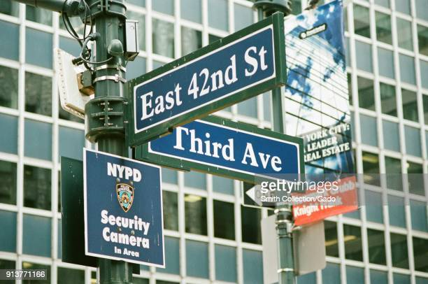 Road sign for the intersection of 42nd Street and 3rd Avenue in Manhattan New York City New York with NYPD surveillance sign also visible September...