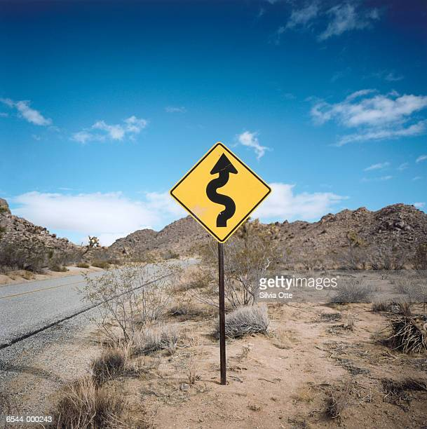 road sign in desert - curved arrows stock photos and pictures