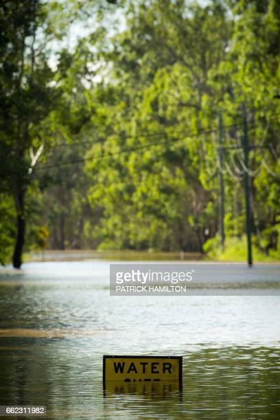 TOPSHOT A road sign is seen partially submerged in floodwaters in North MacLean Brisbane on April 1 2017 Flooded rivers were still rising on April 1...