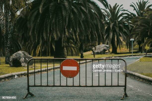road sign on barricade against trees - barricade stock photos and pictures