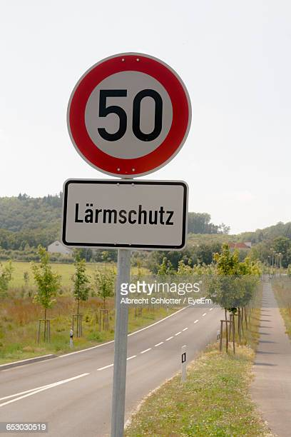 road sign on country road against clear sky - albrecht schlotter stock-fotos und bilder