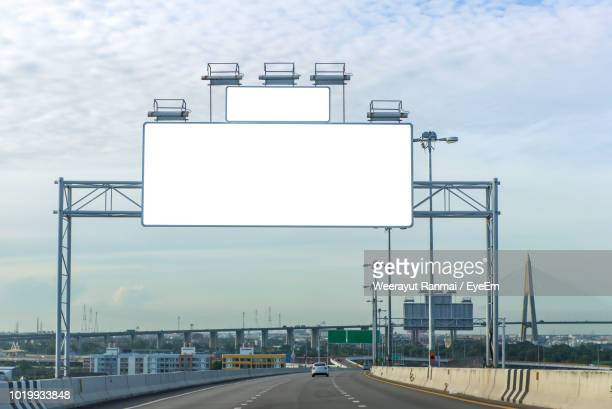 road sign on highway against sky in city - billboard highway stock pictures, royalty-free photos & images