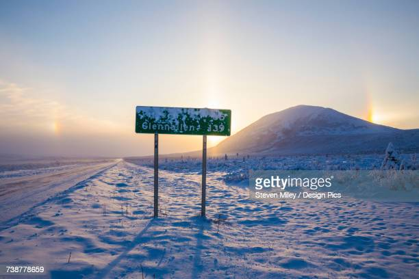 a road sign partially obscured by frost along the richardson highway with parhelia (sundogs) and donnelly dome in the background on a bitterly cold winter day - miley fotografías e imágenes de stock