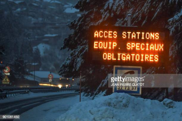 A road sign reading 'Ski Resorts Access Special Gear Compulsory Required' is pictured on a road leading to the French Alps ski resorts of Les...