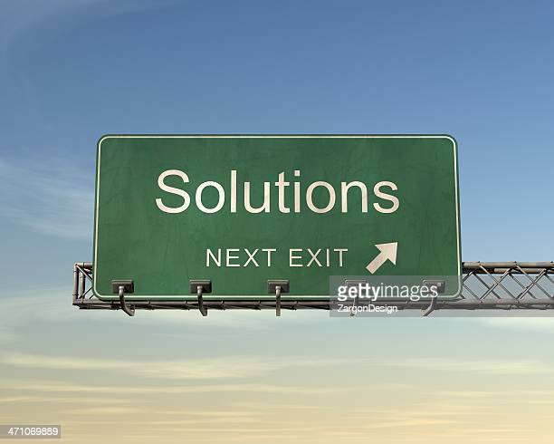 Road sign saying solutions in front of blue sky