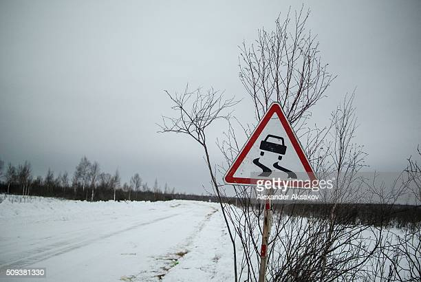 A road sign 'Slippery Road' is seen on a winter road at a market near the Siberia village of Yangutum on February 2 2016 in Siberia Russia Local...