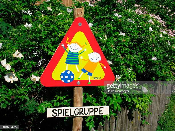 Road sign 'Spielgruppe' with flowering bushes behind, warning drivers to watch out for children, with an overall sunny, summery feel.