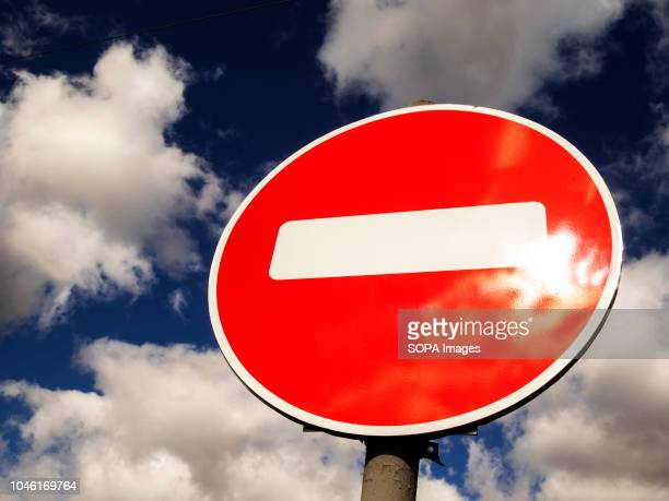 Road sign traffic seen closed on blue sky with clouds.