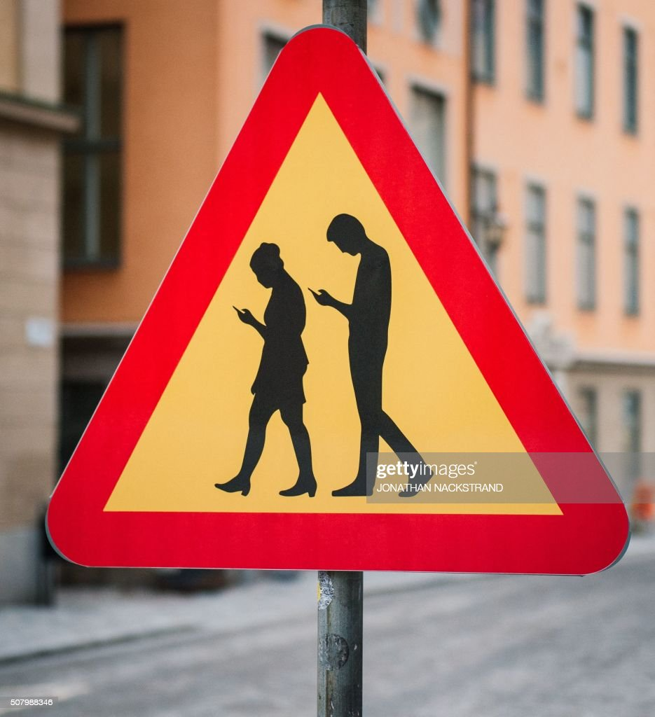 A road sign Warning Against pedestrians focusing on their smartphones is pictured on February 2, 2016 near the old town in Stockholm. / AFP / JONATHAN