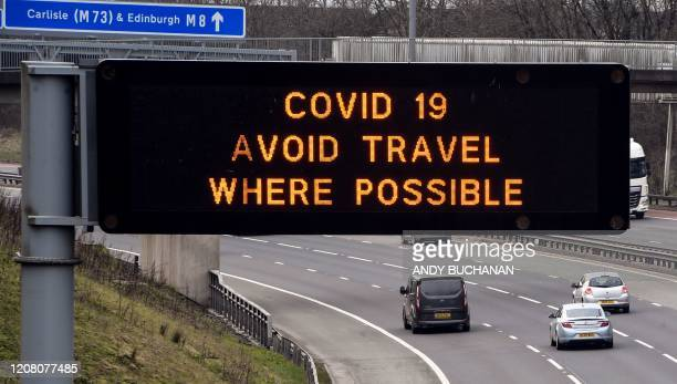 Road sign warns drivers to avoid unecessary travel on the M8 motorway at Easterhouse in the East End of Glasgow in the morning on March 24, 2020...