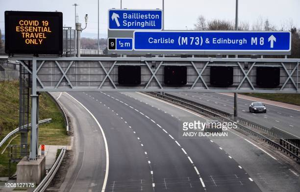 Road sign warns drivers to avoid unnecessary travel on a near-empty M8 motorway at Easterhouse in the East End of Glasgow in the late afternoon on...