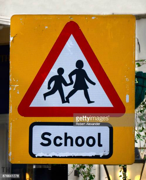 A road sign warns motorists in London England that children may be crossing the road in front of a school