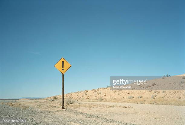 Road sign with exclamation mark in desert