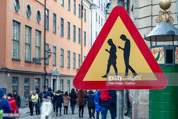 Road Sign With People Walking On Road In Background