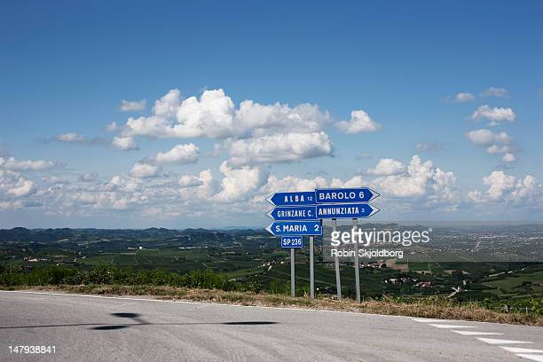 Road signs in front of blue sky with clouds.
