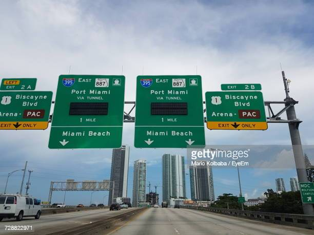 Road Signs On Highway Against Sky In City