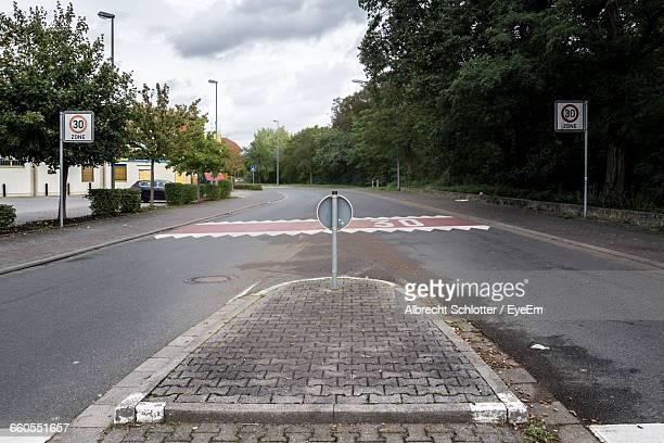 road signs on sidewalk amidst trees - albrecht schlotter foto e immagini stock