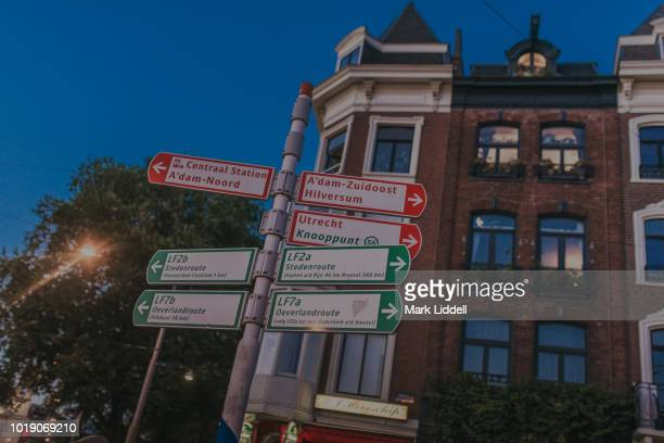 road signs pointing to various destinations on the streets of amsterdams at night. - mark's stock pictures, royalty-free photos & images