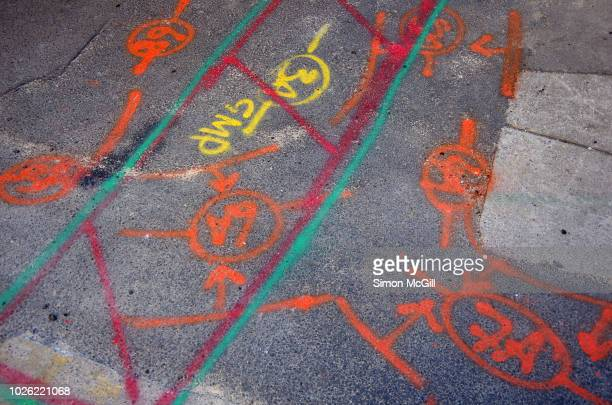 road surveyor spraypainted markings identifying where pipes and other utilities are located on a road undergoing contruction work - marca de rua - fotografias e filmes do acervo