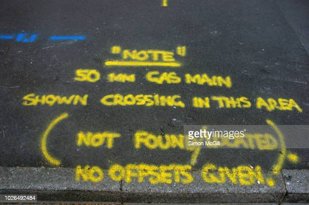 Road surveyor spraypainted markings on a road undergoing contruction work stating 'Note 50mm gas main shown crossing this area (not found/located). No offsets given'