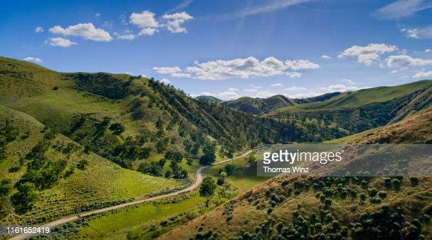 road through a valley from above - mountain stock pictures, royalty-free photos & images