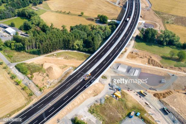 road through agricultural area, construction site - aerial view - parapetto barriera foto e immagini stock