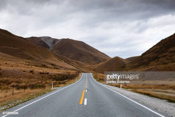 road through desolate landscape in bad weather, new zealand - country road stock photos and pictures