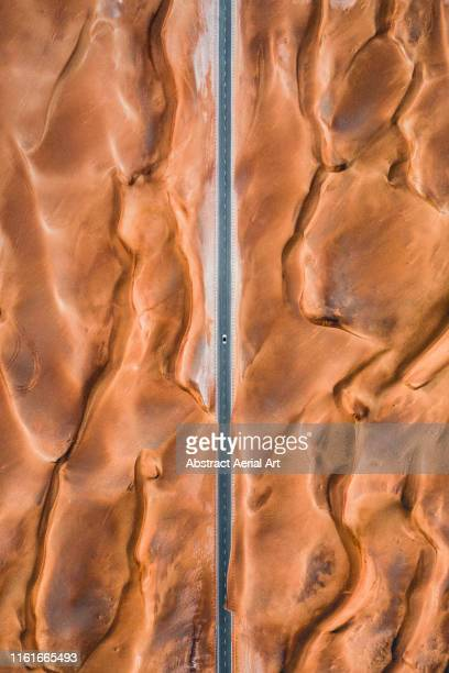 road through the centre of fiery coloured desert patterns shot from above, united arab emirates - drohnenperspektive stock-fotos und bilder