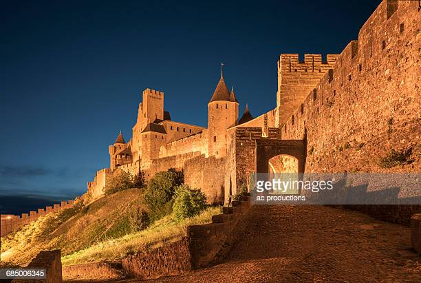 road to castle at night in carcassonne, languedoc-roussillon, france - carcassonne stock pictures, royalty-free photos & images