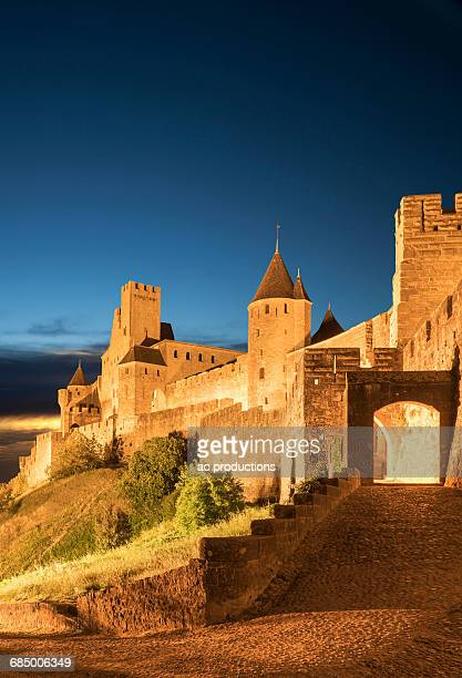 road to castle at night in carcassonne, languedoc-roussillon, france - languedoc rousillon stock pictures, royalty-free photos & images