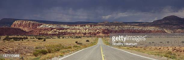 road to mesa's of ghost ranch with storm brewing - timothy hearsum stock-fotos und bilder
