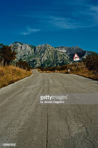 road to mountain - jacopo caggiano stock pictures, royalty-free photos & images