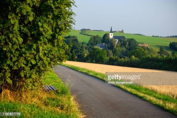 road to village with church - dorp stockfoto's en -beelden