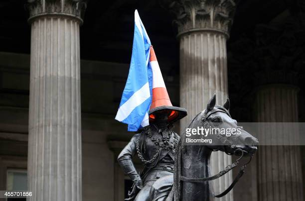 A road traffic cone and a St Andrew's or Saltire flag the national flag of Scotland sit atop a statute of the Duke of Wellington in Glasgow UK on...