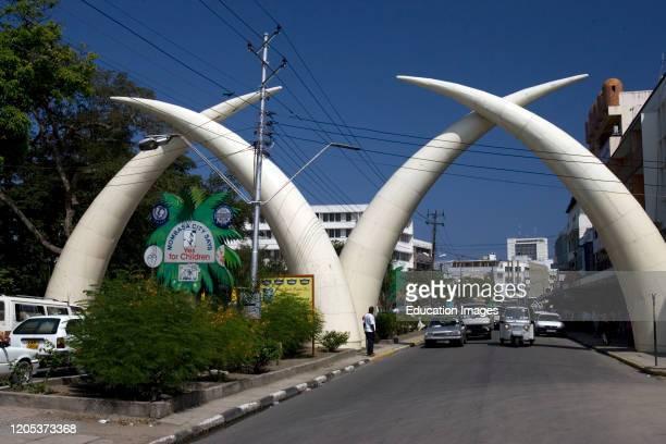 Road traffic passes elephant tusk road arch Mombasa Kenya.
