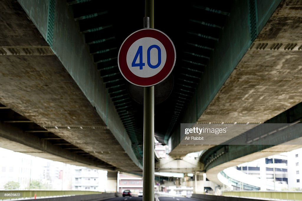 Road traffic sign of road under highway : Stock Photo