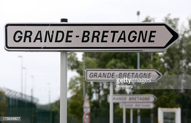 Road traffic signs indicating the direction to Great Britain stand at the Eurotunnel terminal operated by Groupe Eurotunnel SA in Calais France on...