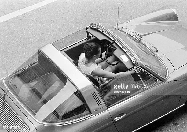 Road traffic, young woman sits in a Porsche Targa with opened sunroof, birds-eye view, aged 20 to 30 years -