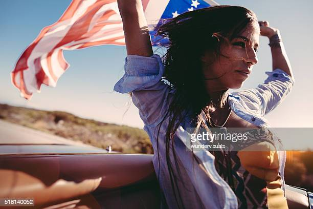 Road Trip boho girl holds American Flag on convertible car