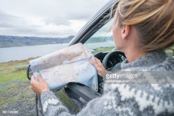 Road trip concept, girl in car looking at map, tourism in Iceland